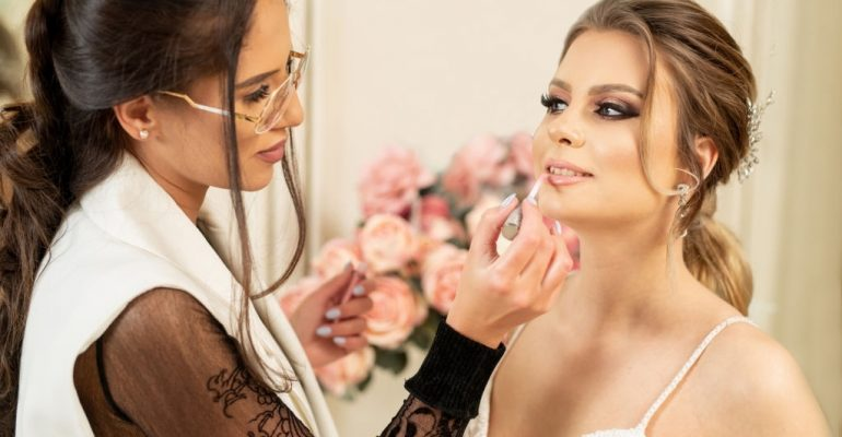 Make up artist applying lip gloss to bride and preparing her for her wedding